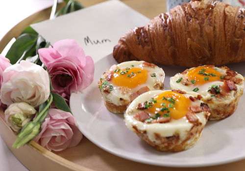 Hash brown egg nests with croissant and flowers on a tray